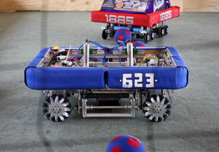 Robots from FIRST Robotics Spar During a Soccer Game