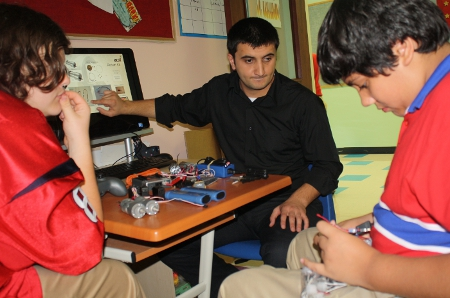 Rahman Rasulzada and students work with electrical components
