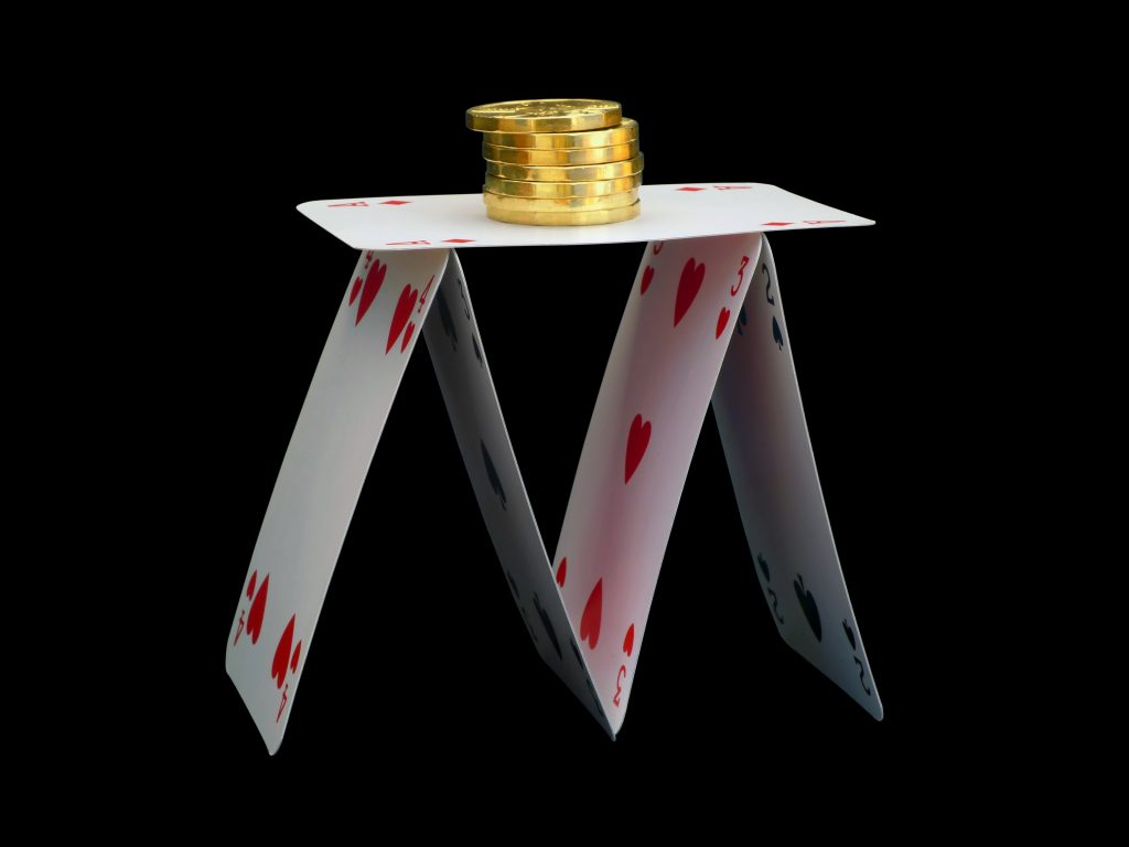 House of cards with gold coins