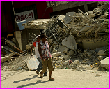 Haitians walks past earthquake damage